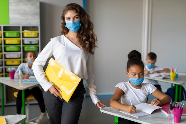 Kids and teacher protecting themselves with medical masks