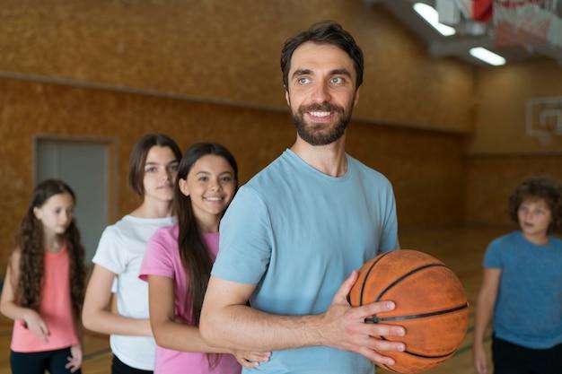Bambini e insegnante con palla da basket a tiro medio