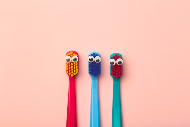 Kids toothbrushes of different colors on pink