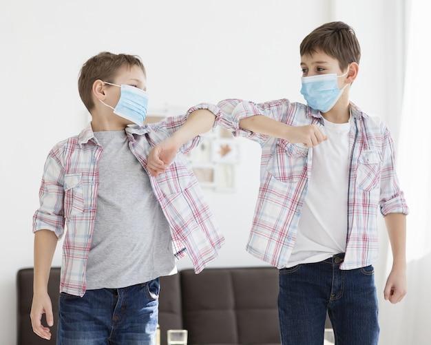医療用マスクを着用しながら肘に触れる子供たち