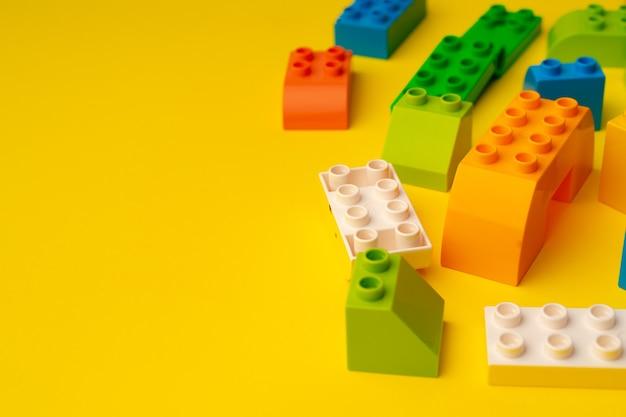 黄色の背景に散らばっている子供のおもちゃコンストラクターの詳細