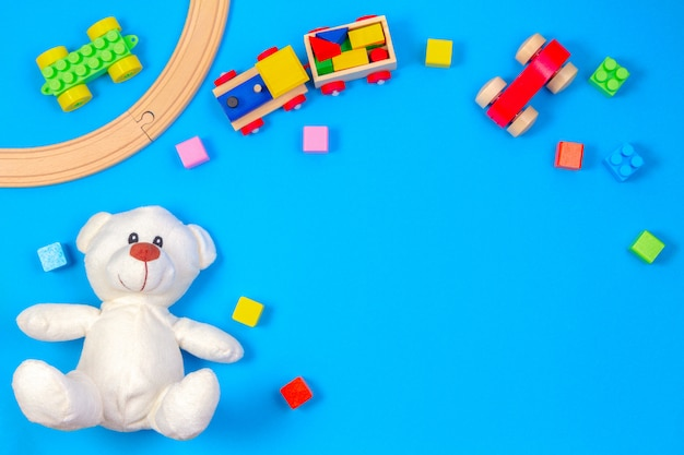 Kids toys background with teddy bear, wooden train and colorful blocks. top view