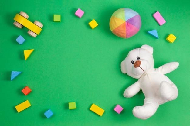 Рамка детских игрушек на зеленом.