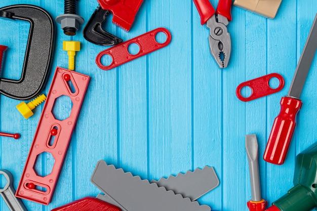 Детские игрушки инструмент на синем фоне деревянных с копией пространства