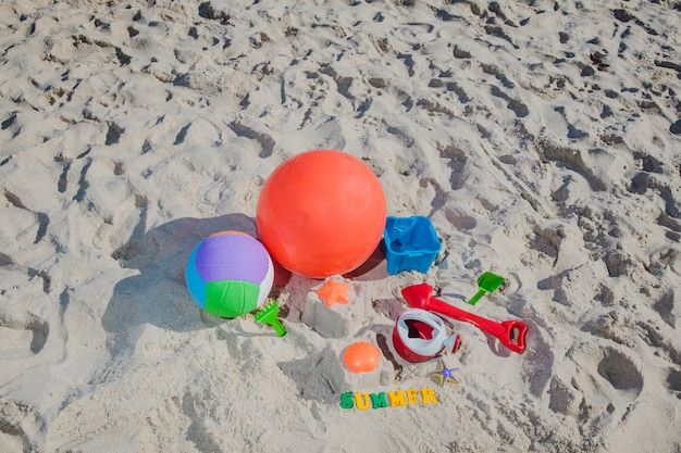 Kids toys on sand in bright sun