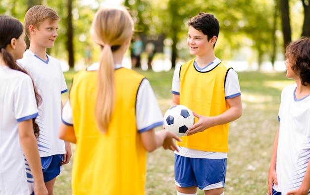 Дети вместе тренируются перед футбольным матчем