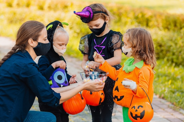 子供たちはハロウィーンの衣装とフェイスマスクでトリックオアトリートをcovid19ハッピーハロウィーンから保護します