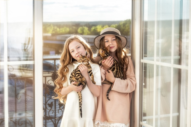 Дети две девочки красивые и счастливые с маленькими милыми бенгальскими котятами вместе