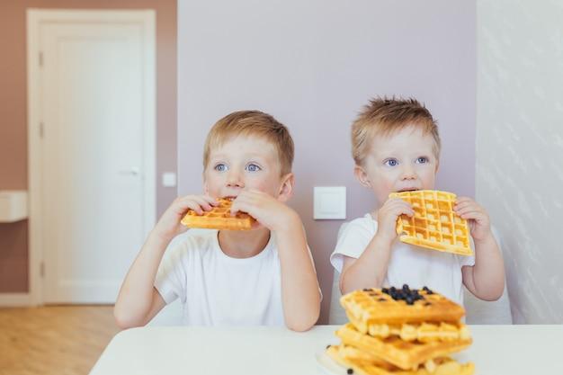 子供たち、キッチンで自宅でワッフルと一緒に朝の朝食を食べる2人の男の子