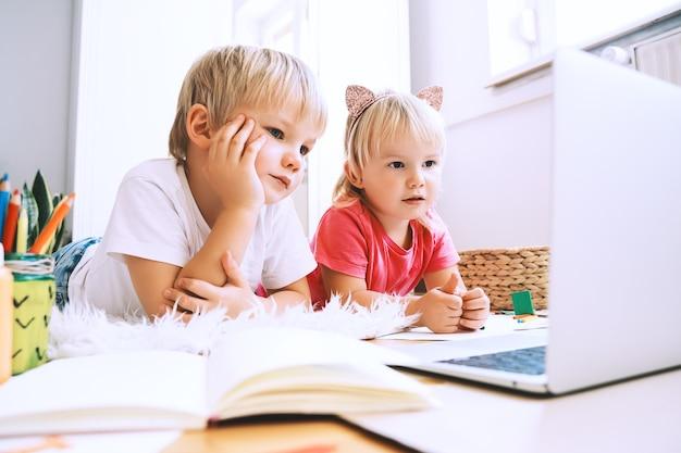 コンピューターのオンライン技術を使用して創造的な芸術を作り、工芸品を作る子供たち子供たちのオンライン教育