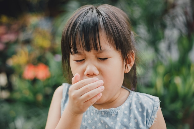 Kids using hand covering her mouth while cough which is incorrect sneezing.