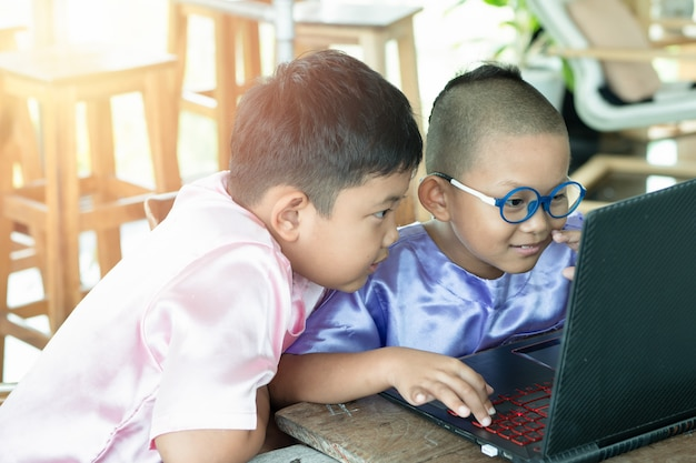 Kids using laptop enjoy, happy at home. education concept