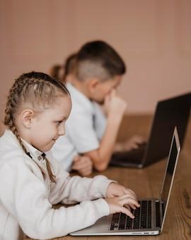 실내에서 노트북을 사용하는 어린이