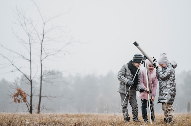 Kids using a telescope outside with copy space