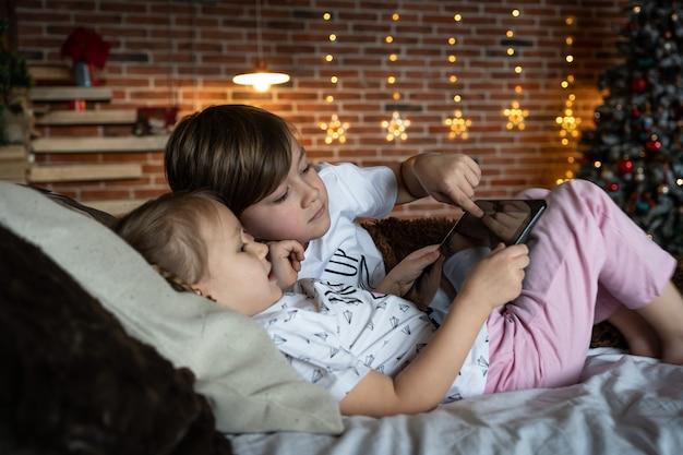 Дети видео маленький мальчик санта шляпа экран компьютера, общение онлайн разные друзья рождественский дом