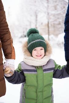 아이들은 첫 눈이 내리는 공원을 걷습니다.