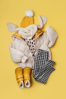 Kids warm puffer jacket with hat and boots on yellow  background. stylish childrens outerwear. winter fashion outfit