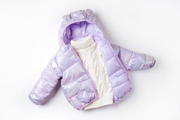흰색 바탕에 후드와 스웨터가 있는 따뜻한 패딩 재킷. 스타일리시한 아동복. 겨울 패션 복장