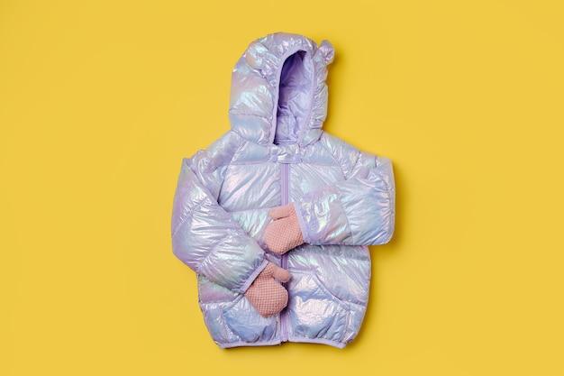분홍색 배경에 후드가 달린 따뜻한 패딩 재킷. 스타일리시한 아동복. 겨울 패션 복장