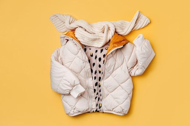 노란색 바탕에 스카프가 달린 따뜻한 패딩 재킷. 스타일리시한 아동복. 겨울 패션 복장