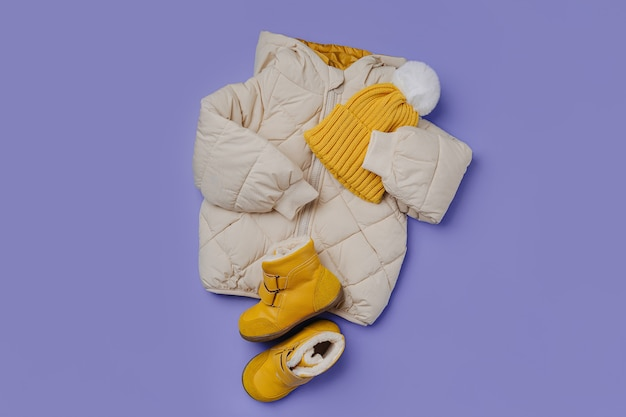 Kids warm puffer jacket with yellow  hat and boots on blue background. stylish childrens outerwear. winter fashion outfit