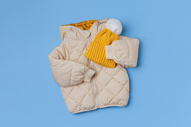 파란색 배경에 노란색 모자가 달린 따뜻한 패딩 재킷. 스타일리시한 아동복. 겨울 패션 복장