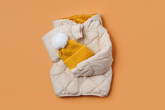 아이들은 주황색 배경에 노란색 모자를 쓴 따뜻한 패딩 재킷입니다. 스타일리시한 아동복. 겨울 패션 복장