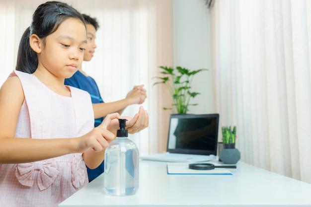 Kids washing hands with alcohol gel sanitizer gel pump dispenser