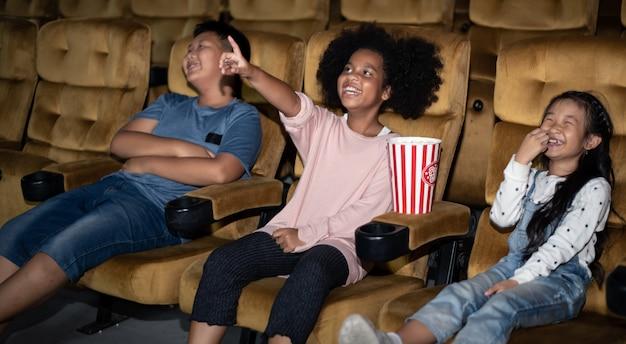 Kids watching movie in cinema in cinema theatre with enjoying.
