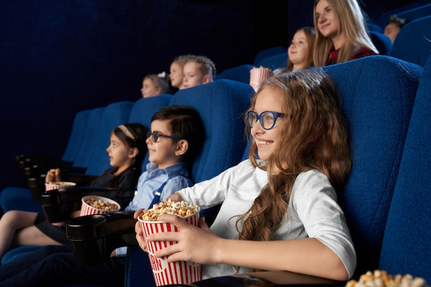 Kids watching movie in cinema, holding popcorn buckets.