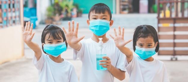 子供がマスクを着用し、コロナウイルスを殺すためにアルコールジェルを持ち、外出しないように手を示す Premium写真