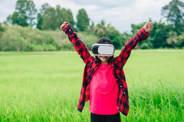 バーチャルリアリティビデオメガネをかけて、美しい自然の背景で楽しい子供たち