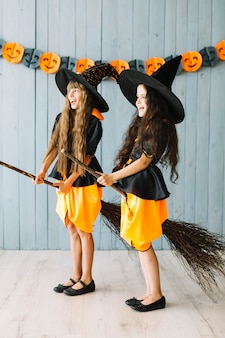 Kids in witch costumes holding broomsticks between legs