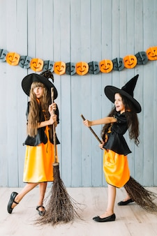 Kids in witch costumes holding broomsticks