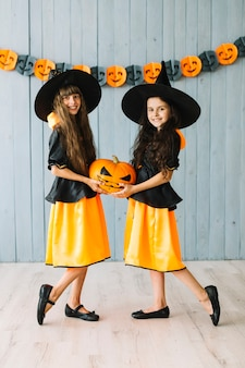 Kids in witch costumes posing and holding halloween pumpkin