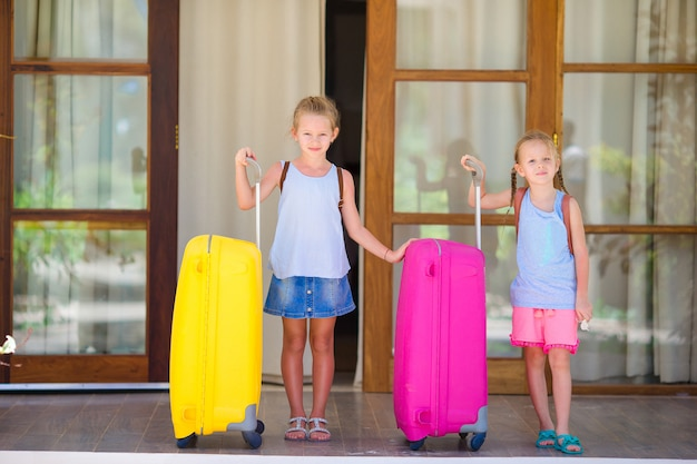 Kids with 2 luggages ready to travel