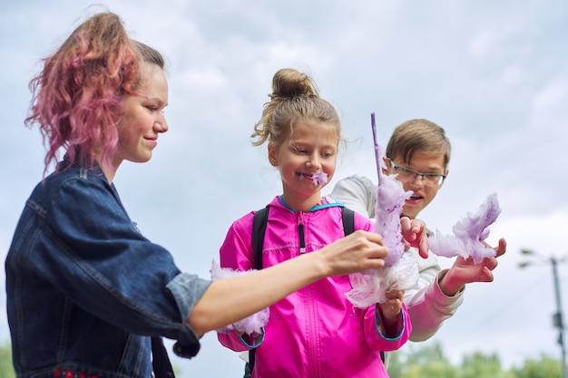 綿菓子を持った子供たち、3人の子供たちが笑って甘い砂糖ピンクの雲を食べています