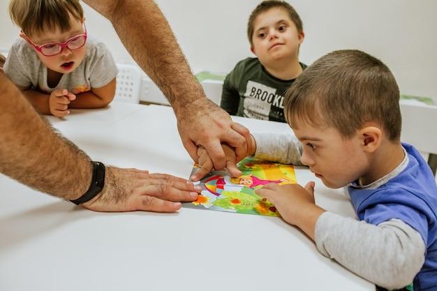 다운 증후군을 가진 아이들이 흰색 책상에 앉아 공부하고 있습니다.