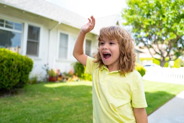 裏庭で変な顔のさようなら手を持っている子供たち。感情的に驚いた興奮した子供。さようならまたはこんにちはサインを持つ小さな男の子。