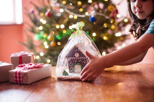 クリスマスの時期にジンジャーブレッドのクッキーハウスを持つ子供たち