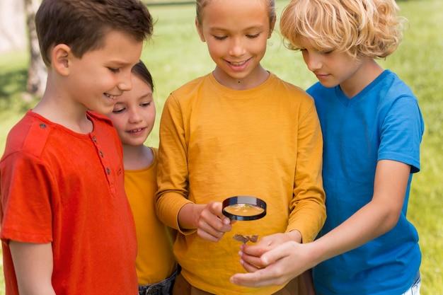 Дети с увеличительным стеклом крупным планом