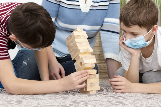 Kids with medical masks playing jenga with mother