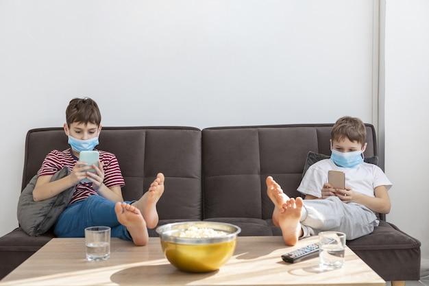 Bambini con maschere mediche che giocano su smartphone a casa