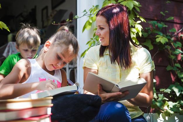ポーチの本を楽しむ母親の子供たち