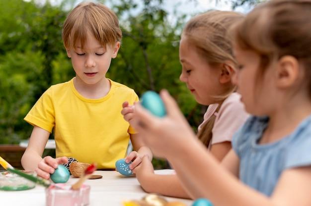 색칠한 계란을 가진 아이들이 가까이 있습니다.