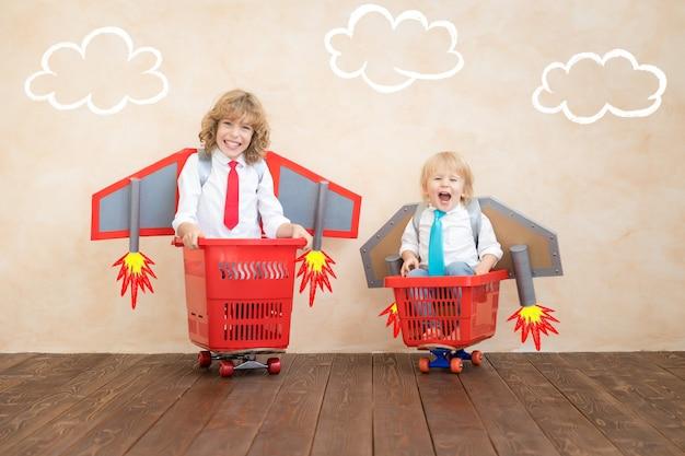 쇼핑 카트 실내에 경주하는 종이 로켓을 가진 아이