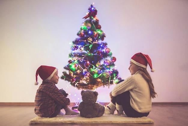 The kids with a teddy bear sit near the christmas tree