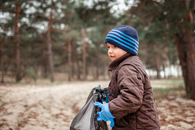 Kids with their father cleaning area in forest