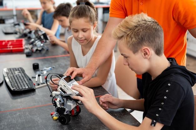 로봇 교육 프로젝트에서 교사와 협력하는 어린이