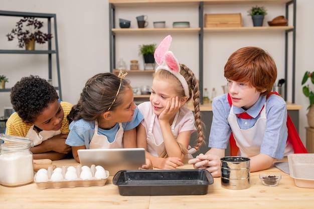母の日に驚きを与えるために、木製の台所のテーブルに立っている間、子供たちはデジタルタブレットの助けを借りてレシピを読んで包みました